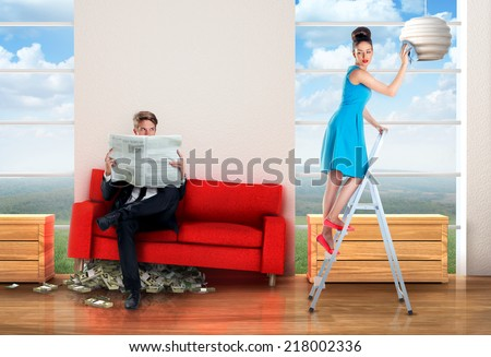 Man sitting on a  money pile while woman is doing chores - stock photo