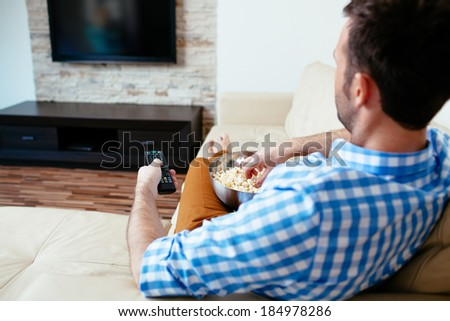 Man sitting on a sofa and holding a remote control