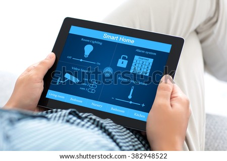 man sitting on a sofa and holding a tablet computer with smart home on the screen - stock photo