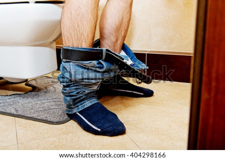 Man sitting on a toilet seat - stock photo