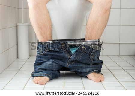 Man sitting on a toilet seat with his pants and boxers down - stock photo