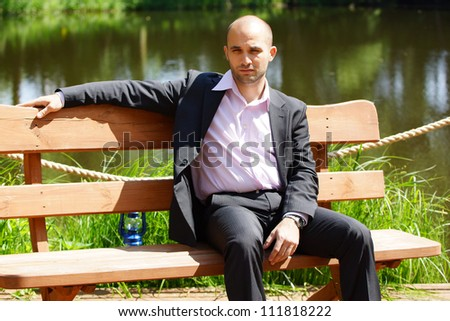 Man sitting on a wooden bench - stock photo