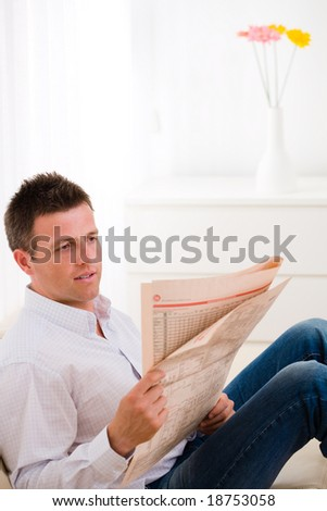 Man sitting on couch at home reading reading newspaper . - stock photo