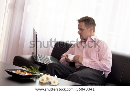 Man sitting on couch using laptop computer at home. - stock photo