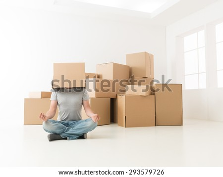 man sitting on floor in new apartment, meditating with box on his head - stock photo