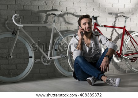 Man sitting on floor, talking on cellphone, two bikes in the background