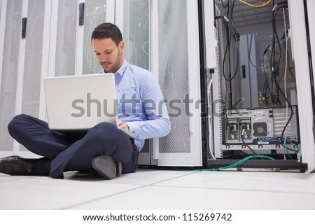 Man sitting on floor with laptop beside servers in data center - stock photo