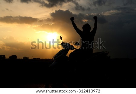 Man sitting on motorcycles sunset