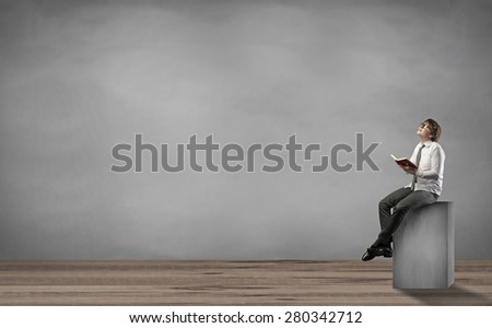 man sitting on pedestal and reading a book
