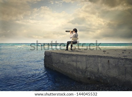 man sitting on pier looking at ocean with telescope