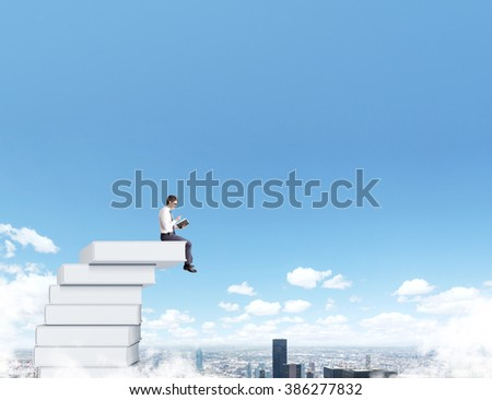 Man sitting on pile of books reading. Blue sky and city at  background. Paris. Concept of reading.