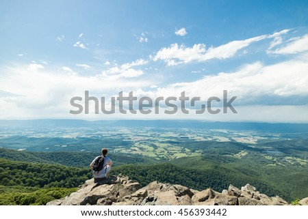 Man sitting on rocky outlook viewpoint over lush green forest in Shenandoah National Park, Virginia, USA - stock photo