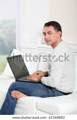 Man sitting on sofa at home with laptop computer