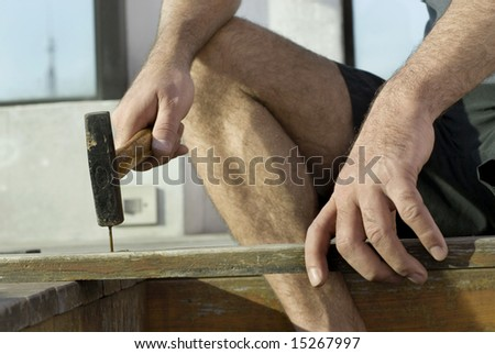 Man sitting on stairs holding board and hammering nail. Horizontally framed shot.