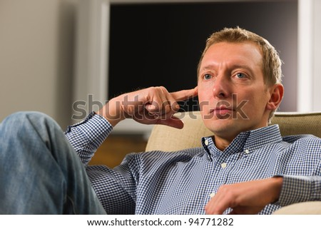Man sitting on the armchair and thinking something. - stock photo