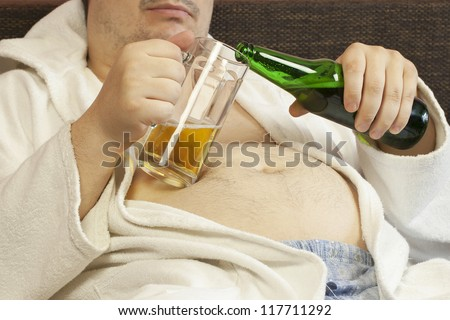 Man sitting on the couch with a beer in the hands of - stock photo