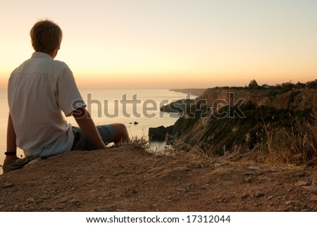 Man sitting on the edge of a cliff, staring at a majestic coastline - stock photo