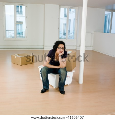 man sitting on the floor inside an empty loft apartement with tax forms and laptop computer - stock photo