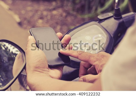 Man sitting on the motorbike using phone black screen - stock photo