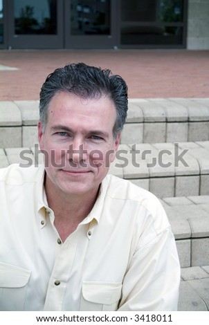 Man sitting on the steps of a building looking happy and friendly. - stock photo