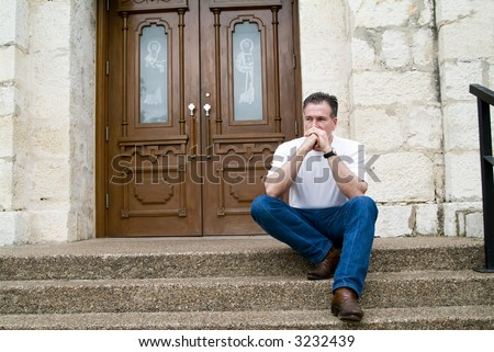 Man sitting on the steps of a church with an anxious expression on his face and in his body posture. - stock photo