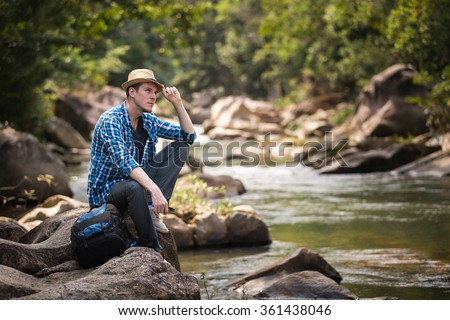 Man sitting on the stone near river in jungle forest. Travel and adventure concept. - stock photo