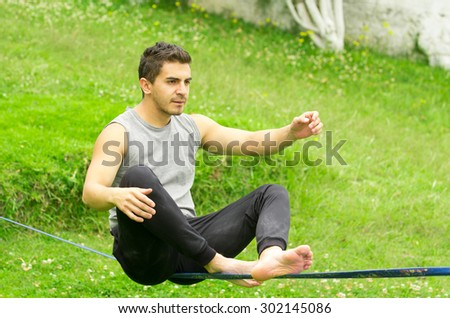 Man sitting on tightrope or slackline left arm to the side concentrating to keep balance with grassy background.