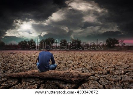 Man sitting on timber on land to the ground dry cracked with storm. - stock photo