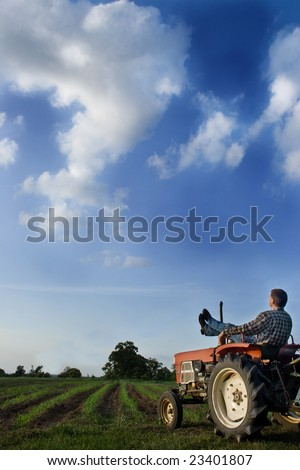 Man sitting on tractor watching corn pop up in rows - stock photo