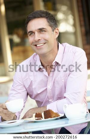 Man sitting outside cafe - stock photo
