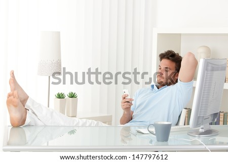 Man sitting relaxing at desk, bare feet on table, texting on mobile phone. - stock photo