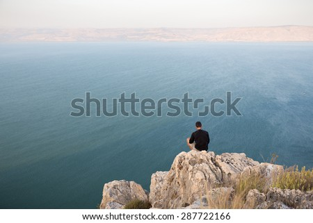 Man sitting resting stone cliff above lake sea, Arbel mountain, Ramat Golan heights, Kineret Galilee Tiberias lake, Israel.
