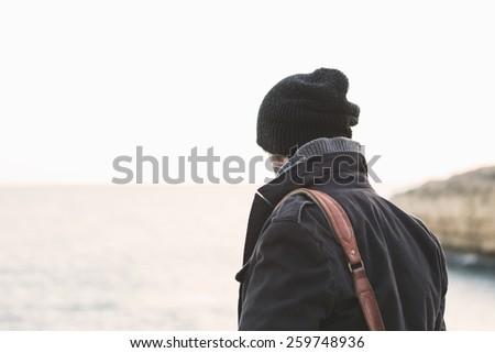 Man sitting the rocks at sunset in winter - stock photo