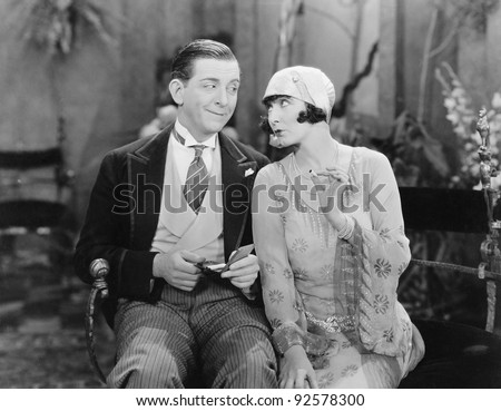 Man sitting with a woman who is holding a cigarette - stock photo