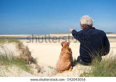 Man sitting with dog on sand dune at Dutch beach on wadden island Texel - stock photo