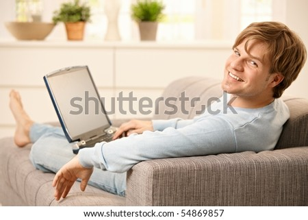 Man sitting with laptop computer on sofa  with feet up in living room, looking back at camera, smiling. - stock photo