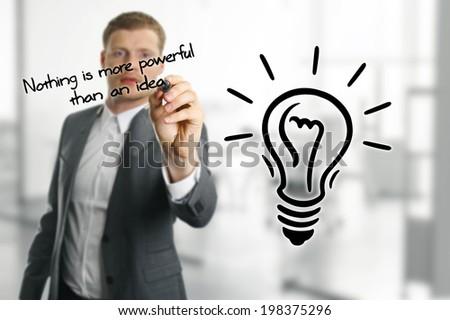 man sketching lightbulb, idea concept - stock photo