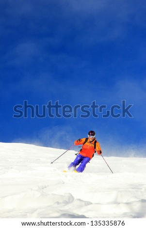 Man skiing fresh snow with blue sky background, Utah, USA. - stock photo
