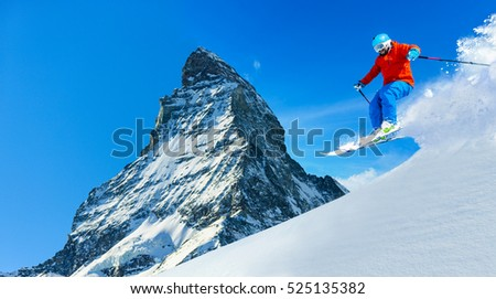 Man skiing in fresh powder snow with Matterhorn in background, Zermatt in Swiss Alps.
