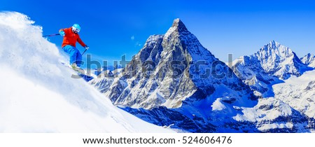 Man skiing on fresh powder snow with Matterhorn in background, Zermatt in Swiss Alps.