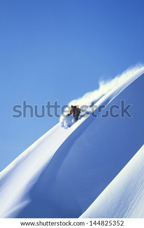 Man skiing on steep slope against clear blue sky - stock photo