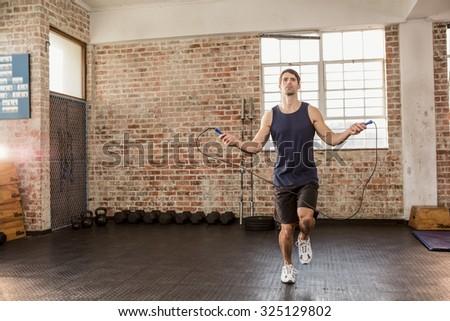 Man skipping wearing sportswear at the gym - stock photo
