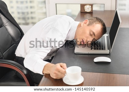 Man sleep on laptop at office with cup - stock photo