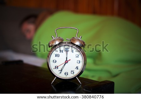 man sleeping and clock close-up in early morning, 7am time for work  - stock photo