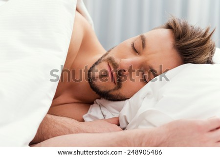 Man sleeping. Handsome young shirtless man sleeping in bed  - stock photo