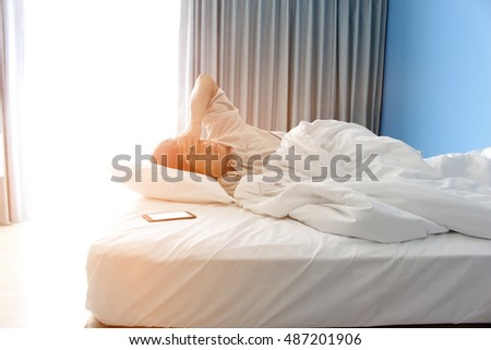man sleeping in bed and a smartphone