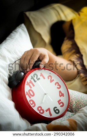 Man sleeping in bed turning off an alarm clock in the morning - stock photo