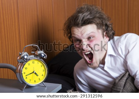 Man sleeping in bed with an alarm