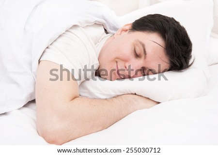 Man sleeping in his bed - stock photo