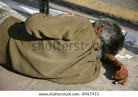 man sleeping on sidewalk, delhi, india - stock photo